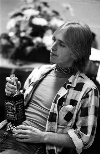 tom petty backstage with whisky bottle wearing a flannel shirt NEW YORK CITY, 1979