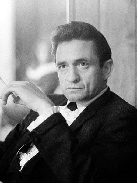 American country music icon Johnny Cash smokes a cigarette backstage at the Circle Star Theatre in San Carlos, CA, December 1967. His wife, June Carter Cash, is in the background.