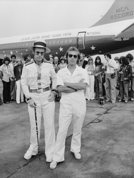 English pop star and pianist Elton John and his lyricist Bernie Taupin pose in front of their private Boeing jet on a runway in California, during Elton's 1974 US tour. Behind them are some of the 35 musicians, roadies and other personnel who accompanied the tour. (Photo by Terry O'Neill/Getty Images)