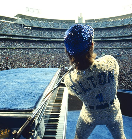 English singer songwriter Elton John performing at Dodger Stadium in Los Angeles, 1975. He is wearing a sequinned baseball outfit.