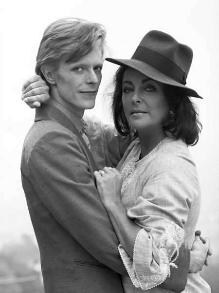 Singer David Bowie shares a cigarette with actress Elizabeth Taylor in Beverly Hills, 1975. It was the first occasion that the pair had met.