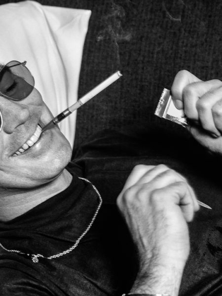 Hunter S Thompson laying down on a couch smoking a cigarette at the Gramercy Hotel in NYC in 1977