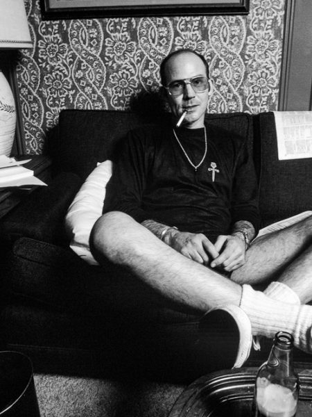 Hunter S Thompson sitting on a couch smoking a cigarette at the Gramercy Hotel in NYC in 1977